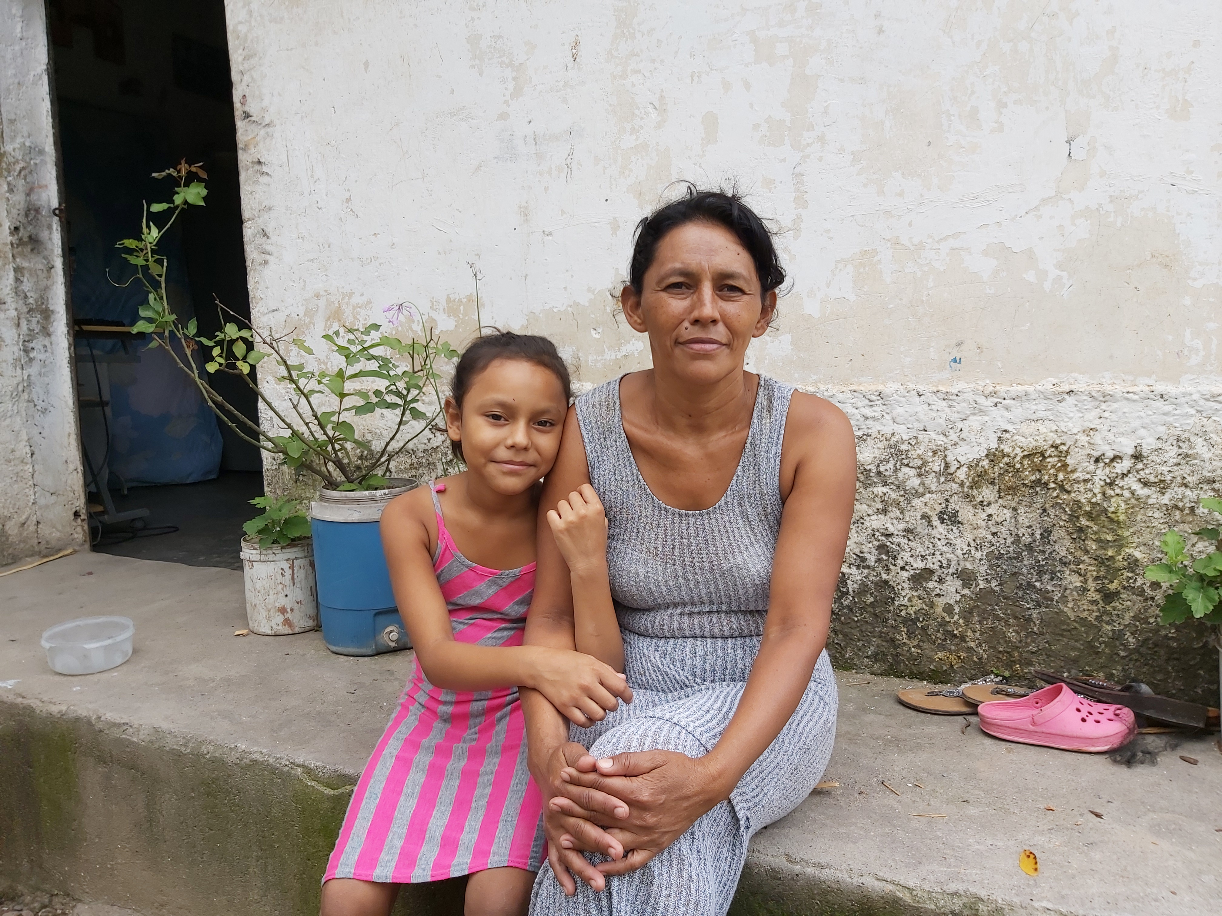 Beneficiaria Daysi Castro junto a su hija frente a su casa en Comayagua